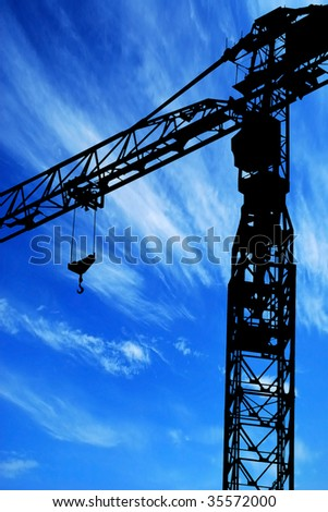 Crane silhouette in blue sky background - stock photo
