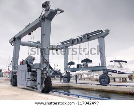 Crane to lifting boats at harbor or marina - stock photo