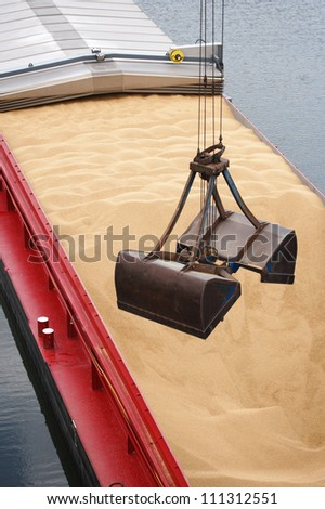crane unloading a barge filled with sand, closeup of shovel - stock photo