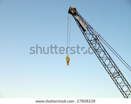 Crane with a hook on a clear, blue sky background and lots of copy-space - stock photo