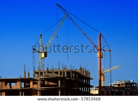 Cranes against a background of construction - stock photo