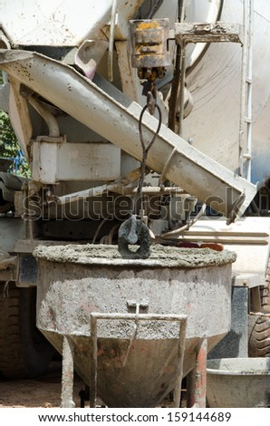 Cranes and buckets of cement for the construction of a building. - stock photo