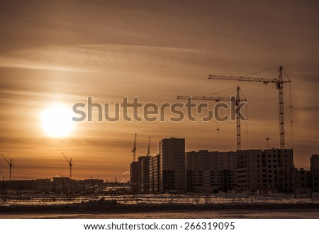 Cranes and building construction site against sunset sky. - stock photo