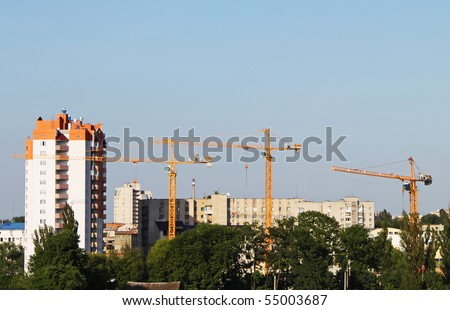 Cranes and building on a background blue sky