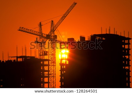 cranes and buildings under construction against the setting sun - stock photo