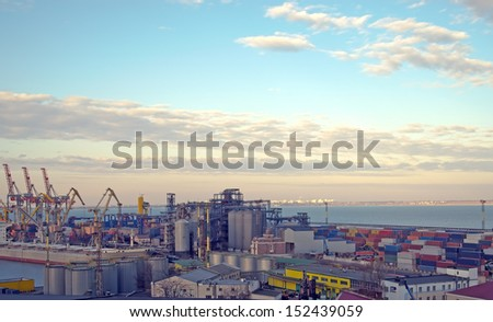 Cranes and containers at a port in the late afternoon period - stock photo
