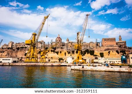 cranes and docks on the shore Cospicua near Valletta in Malta - stock photo