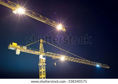 cranes and illumination at night, construction site - stock photo