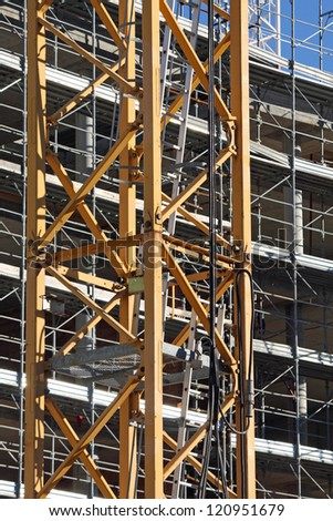 cranes and scaffolding during construction of a building on a construction site