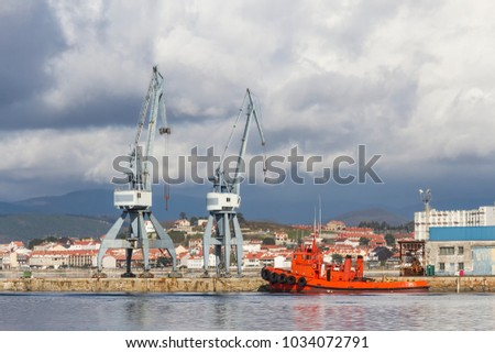 Cranes and tugboat on Vilagarcia de Arousa commercial harbor