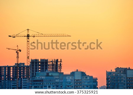 Cranes at construction site in the colorful sunset - stock photo