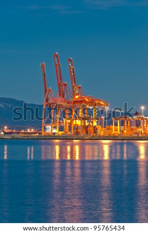 Cranes at the container port terminal dawn (night) time in Vancouver BC - stock photo