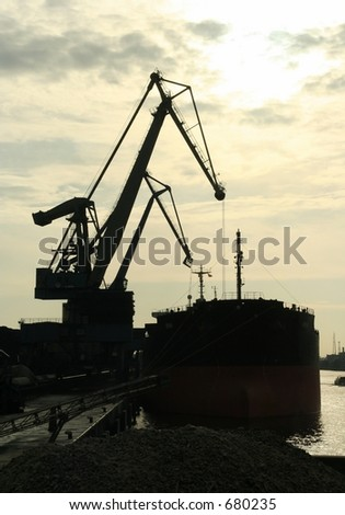 Cranes in a harbor loading a ship