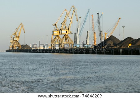 cranes in a port, unloading a ship