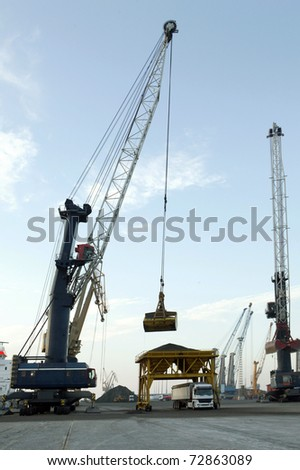 Cranes in a seaport, unloading a ship - stock photo