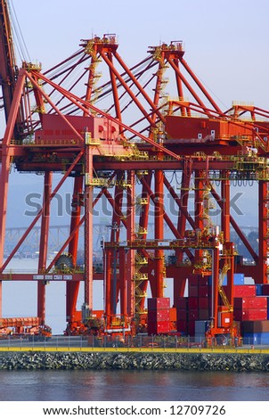 Cranes in red at an industrial port with a bridge in the back - stock photo