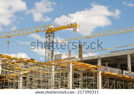 Cranes on construction site at a bright sunny day. - stock photo