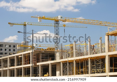 Cranes on construction site at sunny day. - stock photo