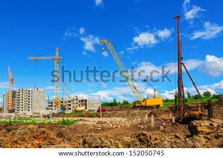 Cranes on the construction site beneath blue cloudy sky