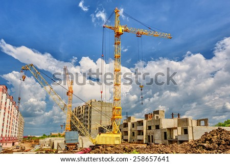 Cranes on the construction site beneath blue cloudy sky - stock photo