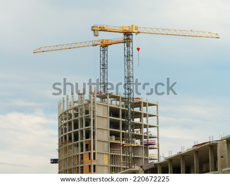 Cranes over the unfinished building on construction site. - stock photo