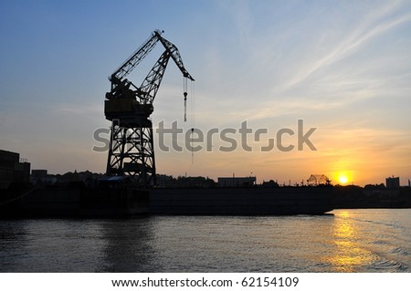 cranes silhouette at sunset by the sea - stock photo