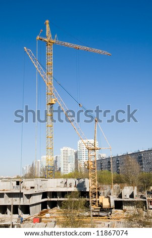 Cranes working on a building site in city