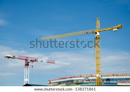 Cranes working on building a house. - stock photo