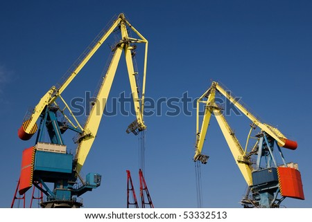 Cranes working under the clear blue sky