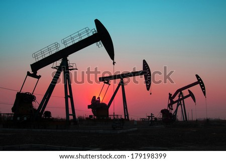crank balanced beam pumping unit under the curtain of night in the JiDong oilfield, on December 1, 2013, caofeidian, hebei province, China.   - stock photo
