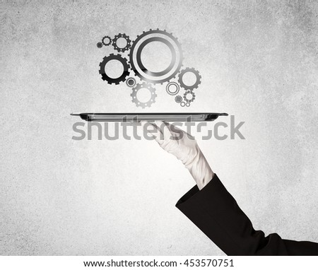 Crank wheel machine working concept with racks served on silver plate by hand in white glove and industrial grey wall pattern background. - stock photo