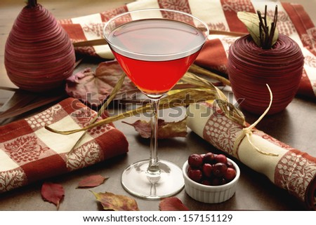 Crantini cocktail or cranberry cocktail with fall or autumn themed background for Thanksgiving or Christmas - stock photo