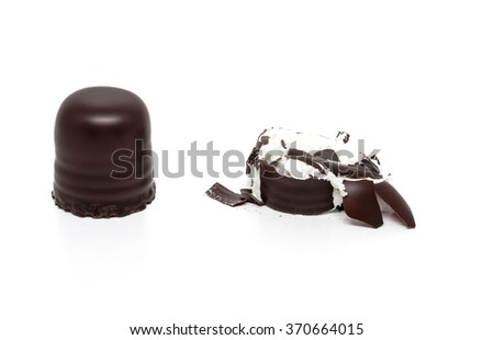 Crash test dummies - two chocolate covered marshmallows, one smashed. Isolated on white background with clipping path - stock photo