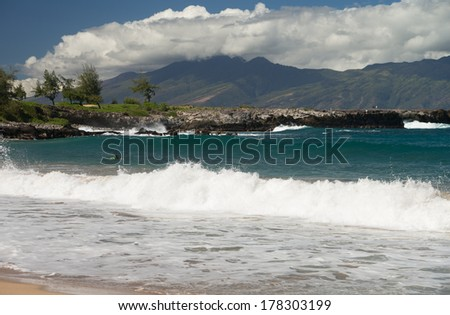 Crashing waves and scenic island views at DT Fleming Beach Park on the beautiful Hawaiian island of Maui - stock photo