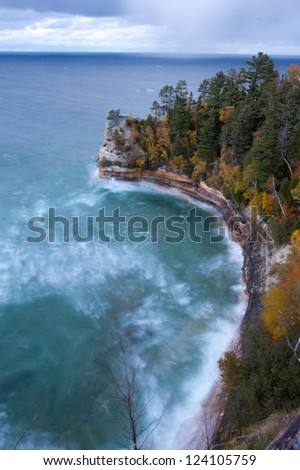 Crashing waves on rocky shoreline with autumnal trees - stock photo