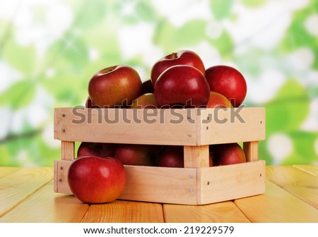 Crate with the red apples on wooden table - stock photo