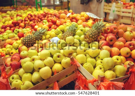 Crates with various sorts of apple and pineapple fruit on farmers market