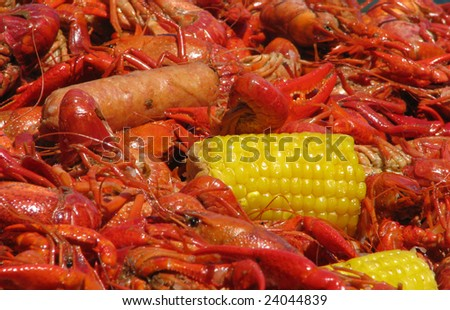 Crawfish, corn and suasage spread out on table. - stock photo