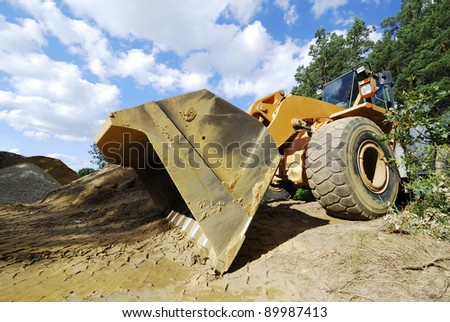 Crawler excavator digging at the edge of a forest