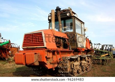 Crawler tractor with a plow on the background of the old agricultural machinery