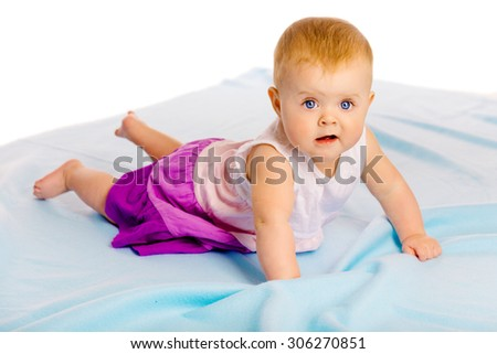 Crawling across the blue plaid baby girl looking at the camera - stock photo