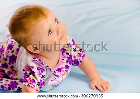 Crawling across the blue plaid baby girl looking up - stock photo