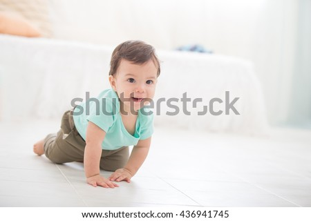 crawling baby boy on living room floor and he smile to you, caucasian child
