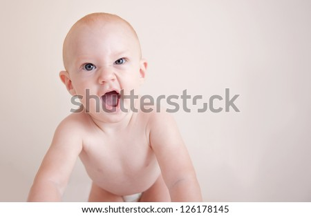 Crawling baby boy with mischievous expression - stock photo