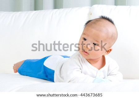 crawling beautiful baby boy on sofa