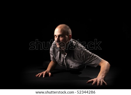 crawling man over dark background - stock photo