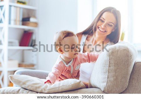 Crawling on sofa. Little baby girl crawling on sofa and leaning on cushion while her mother sitting at background - stock photo