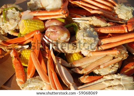 Crayfish and opilio crab legs with hearty vegetables medley served at dusk with shallow DOF - stock photo