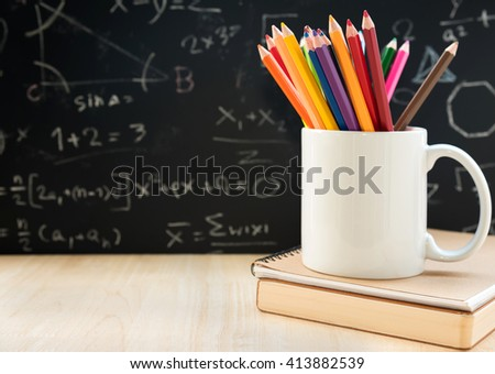 Crayon and book on school table - stock photo