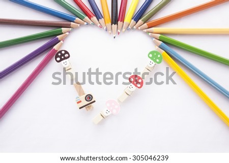 Crayon heart - Heart shape made of colored pencils and binder clip on white background - stock photo
